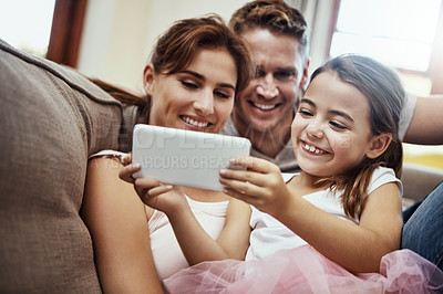 Buy stock photo Shot of a little girl taking a selfie with her parents at home