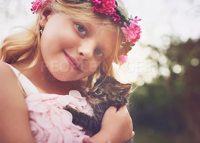 Buy stock photo Shot of a happy little girl holding a kitten and looking at the camera outside in the nature