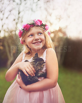Buy stock photo Shot of a happy little girl holding a kitten and looking into the distance while standing outside in nature
