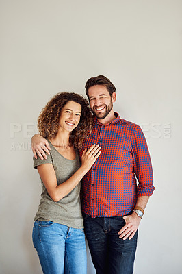 Buy stock photo Portrait of a happy and loving young couple standing together against a gray wall
