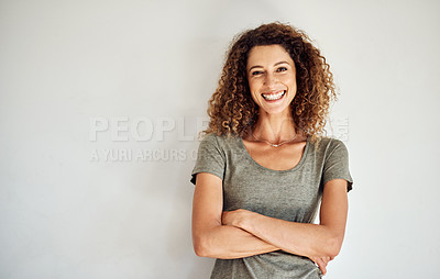 Buy stock photo Portrait of a happy and confident young woman standing posing against a gray wall