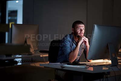 Buy stock photo Shot of a businessman using a computer during a late night at work in a modern office