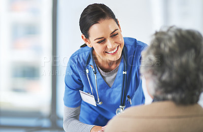 Buy stock photo Shot of a friendly young nurse chatting with her elderly patient while she sits in a wheelchair in the healthcare center