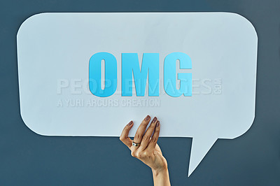 "Buy stock photo Cropped studio shot of a woman holding up a speech bubble with a ""OMG"" on it against a gray background"