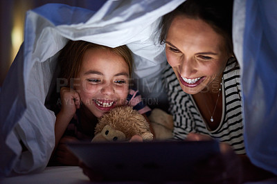 Buy stock photo Cropped shot of an attractive young woman reading her daughter a bedtime story