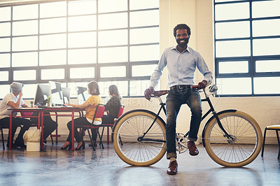 Buy stock photo Shot of a handsome man on a bicycle in a modern office