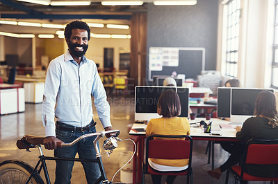 Buy stock photo Shot of a handsome man with a bicycle in a modern office