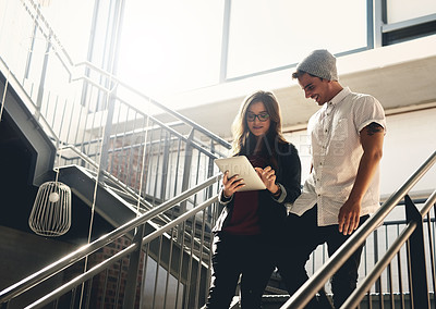 Buy stock photo Low angle shot of two young designers looking at a digital tablet while walking down a flight of stairs