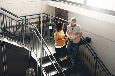 Buy stock photo High angle shot of two young designers looking at a digital tablet while walking down a flight of stairs
