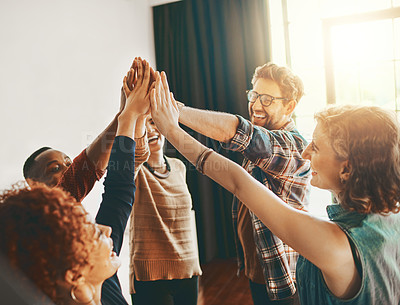 Buy stock photo Shot of creative employees giving each other a high-five in the office