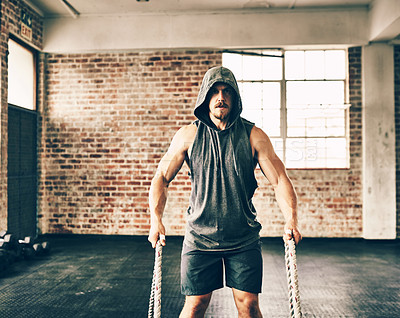 Buy stock photo Shot of a hooded and determined young man making use of ropes to workout in the gym