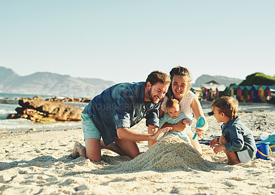 Buy stock photo Shot of a young family spending quality time at the beach
