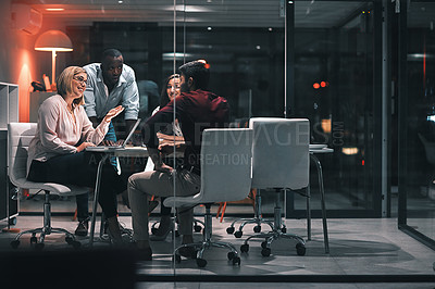 Buy stock photo Shot of colleagues having a meeting during a late night in a modern office