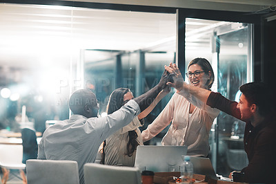 Buy stock photo Shot of colleagues giving each other a high five during a meeting in a modern office