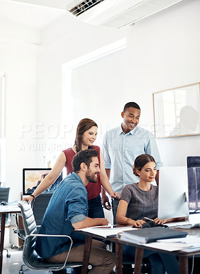 Buy stock photo Shot of a group of colleagues using computer together in a modern office