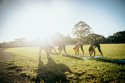 Buy stock photo Shot of a group of women doing yoga together on a field