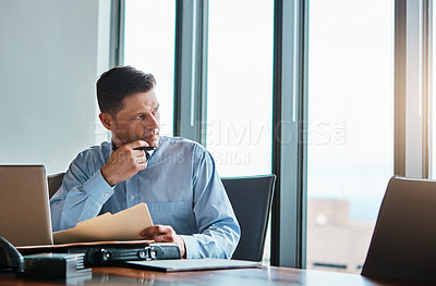 Buy stock photo Shot of a mature businessman working at his desk