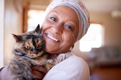 Buy stock photo Cropped shot of a mature muslim woman spending time with her cat