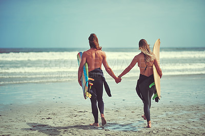 Buy stock photo Rearview shot of a young couple walking on the beach with their surfboards