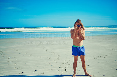 Buy stock photo Shot of a young man spending the day at the beach