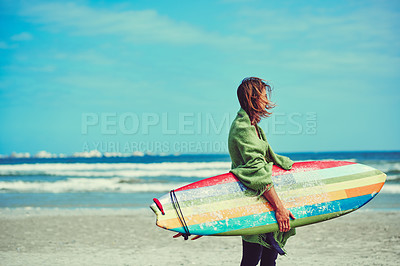 Buy stock photo Shot of a young surfer strolling on the beach with his surfboard