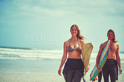 Buy stock photo Shot of a young couple walking on the beach with their surfboards