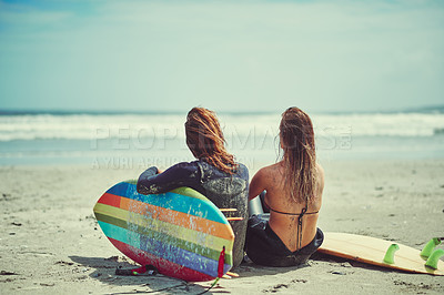 Buy stock photo Shot of a young couple surfing at the beach