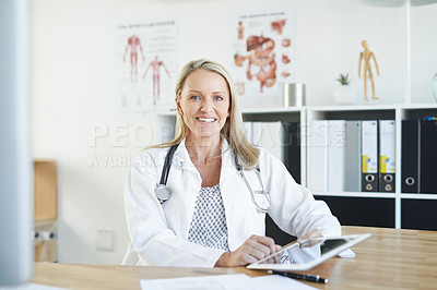 Buy stock photo Portrait of a mature doctor using a digital tablet in a consulting room