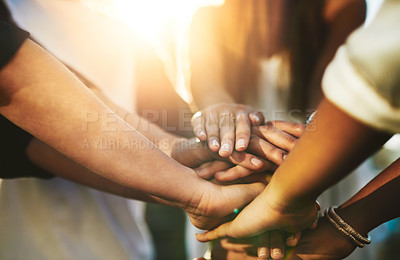 Buy stock photo Cropped shot of an unrecognizable group of people putting their hands together in unity outside
