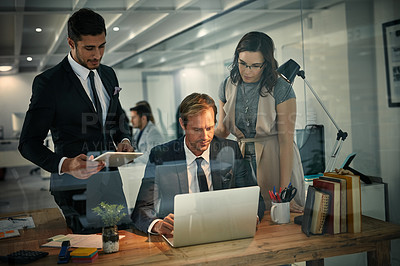 Buy stock photo Shot of a team of colleagues using a laptop together on a night shift at work