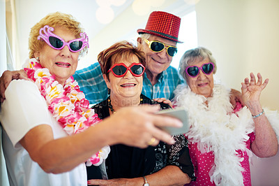 Buy stock photo Shot of a group carefree elderly people wearing glasses and looking at the camera inside of a building