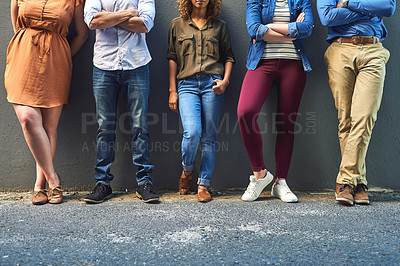Buy stock photo Shot of a group unrecognizable people leaning against a wall while posing for a photo outside