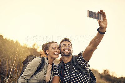 Buy stock photo Shot of a happy couple taking a selfie while out on a hiking trip