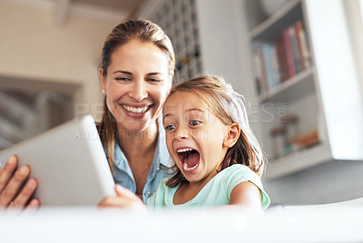 Buy stock photo Shot of an adorable little girl using a digital tablet with her mother at home