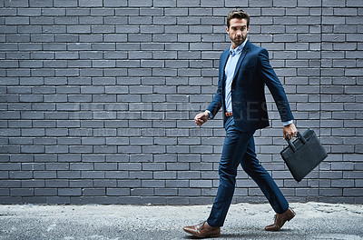 Buy stock photo Shot of a handsome young businessman standing against a grey facebrick wall