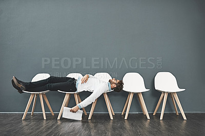 Buy stock photo Shot of a young man lying down on a row of chairs while waiting in line for a job interview