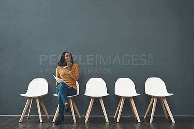 Buy stock photo Shot of a young woman yawning while waiting in line for a job interview