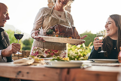 Buy stock photo Shot of a unrecognizable person serving roast chicken over a dinner table outside