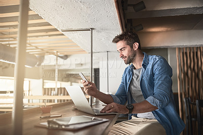 Buy stock photo Shot of a handsome young man using a laptop and phone in a coffee shop