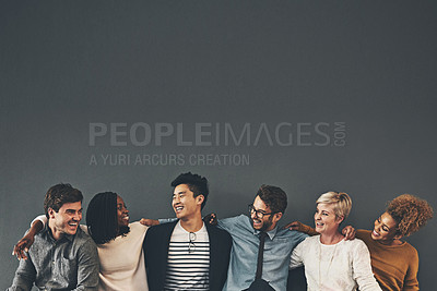 Buy stock photo Studio shot of a diverse group of creative employees embracing each other against a grey background
