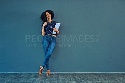 Buy stock photo Studio shot of a young woman holding a book and looking thoughtful against a gray background