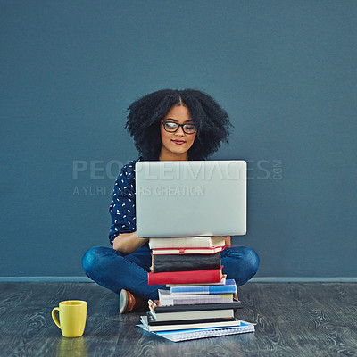 Buy stock photo Studio shot of a young woman using a laptop with books stacked in front of her against a gray background