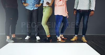 Buy stock photo Cropped studio shot of a group of people standing behind blank paper against a gray background