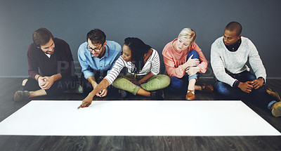 Buy stock photo Studio shot of a group of people sitting on the floor and working on blank paper against a gray background