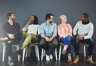 Buy stock photo Studio shot of a group of young people waiting in line on chairs and chatting against a gray background