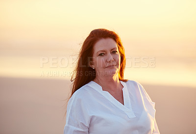 Buy stock photo Shot of mature woman standing on the beach at sunset