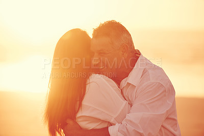 Buy stock photo Cropped shot of an affectionate mature couple embracing on the beach at sunset