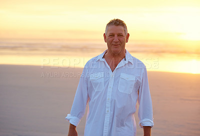 Buy stock photo Shot of mature man standing on the beach at sunset