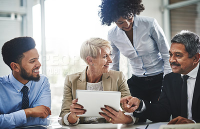 Buy stock photo Shot of a group of businesspeople discussing something on a digital tablet in a meeting