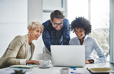Buy stock photo Shot of a group of businesspeople working together on a laptop